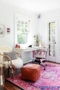 home office space with bright pink and blue rug, leather ottoman, patterned desk chair, white desk, and rattan chair with fur and pillow
