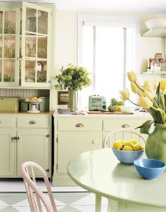 pretty mismatched cabinets in pale sage green with painted floor