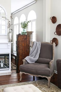 A brown velvet wingback chair with a gray blanket draped over the side, wicker baskets hanging from the wall, and a vintage wooden dresser in the background.