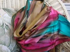 This gorgeous multi colored streaked scarf is hand painted and is 100% silk. Hand hemmed as well. Chestnut, hot pink, seabreeze, and havanis all intertwine to create a lovely combination of colors that will add some rich and vibrant tones to your Spring and Summer. Lovely mixture of colors dripping into each other to create a lovely picture for you to wear with your favorite outfit. Picture this on a khaki or white summer outfit. This scarf is 11 x 58-60 (27.940 cm x 147.32cm-152.40 cm)…