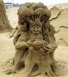 Sand Sculpture  A tree with face holding nest of egg and a bird perched in the branches