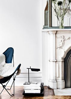 butterfly chair / lighting / sheepskin / mags / grand fireplace and flowers