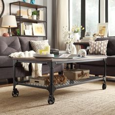 This modern coffee table features wheels, a weathered top and sturdy metal base with shelf for extra storage. This contemporary cocktail table combines classic style with modern flair and will fit in perfectly with any home decor.