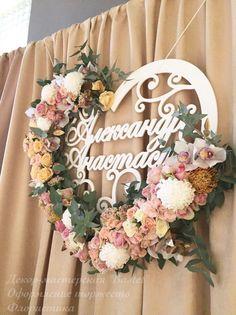 Сердце из дерева с именами жениха и невесты, украшенное живыми цветами.