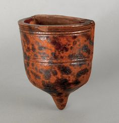 "Pook & Pook.  October 30th 2010.   Lot 374.  Estimated: $300 - $500.   Realized Price: $148.   Pennsylvania redware wall pocket, 19th c., with manganese splash decoration, 6 1/2"" h., 5 1/2"" w."