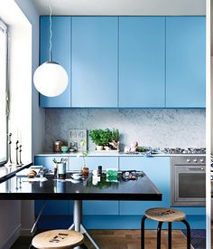 The azure-painted cabinets really pop against the white marble with grey veins and creates a cheery atmosphere.