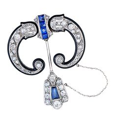Created in the Egyptian Revival style, the pin consists of a pair of inverted diamond-set horns surrounded by a 1.3 mm wide band of black enamel connected to a diamond center set with 4 French-cut sapphires. The bottom of the pin is set with 1 modified rectagular French-cut sapphire surrounded by diamonds. Circa 1930