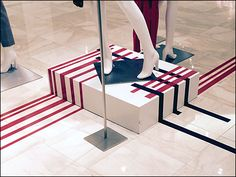 Here Escada® interlaced multicolor linear arrays focus on the mannequin group. The up-and-over on the low pedestal better defines the actual center and point of merchandising focus. The Escada® out...