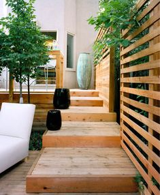 Deep wooden deck stairs with black containters // Joel Loblaw