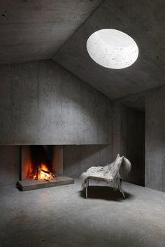 Concrete space + fireplace + circular skylight.