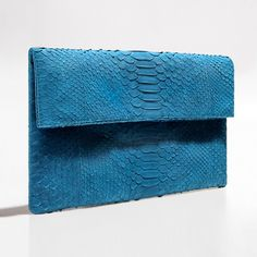 Turquoise blue python clutch by Verinosa This beautiful red python clutch is a classic accessory that exudes a quiet charisma of its own. Work yours throughout the seasons ¨C the vibrant red hue is perfect for revitalizing basics.Designer Colour: Vibrant RedGenuine Python snakeskin: IndonesiaInterior: Suede lining and debossed designer letteringMagnetic-fastening front flapAvailable with and without removable chain strapDimensions: 26.5cm x 15cmNote: This product is handmade. Any differences…