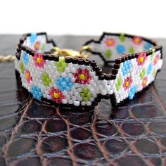 Colorful beaded peyote bracelet with small flowers in green, pink and turquoise.