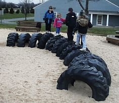 Large tractor tires (worn smooth and obviously recycled) half-buried in the ground (which in turn is covered with sand or wood chips) form a climbing structure.