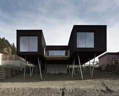 Black-painted S House by Hammerschmid Pachl Seebacher raised up on stilts. Exterior walls are clad with roughly sawn spruce and were painted matte black using traditional Swedish Falu Rödfarg paint. Bungalow, Residential Architecture, Interior Architecture, Black Architecture, Raised House, House On Stilts, Wooden House, Design Case, Modern House Design