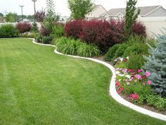 Landscaping in a curved bed along a   privacy wall-- may be a perfect idea for the back yard.