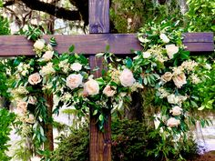 "This beautiful wood cross was hand made by the groom, for he and his bride to stand in front of and say their ""I do's"". We made this gorgeous garland from local greenery and spring blooms that we foraged along the river and complimented it with various garden roses, eucalyptus and other flowers."