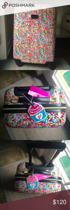 Betsey Johnson Sprinkles Small Roller Luggage Super fun, authentic Betsey Johnson small roller luggage/carry-on. Decorated in colorful sprinkles front and back, it's sure to remind you to stay carefree as you travel to your next destination! Lighweight PVC (5 lbs). Gold-tone hardware. Top handle with extendable pull handle. Logo detail in front. Four pivoting base wheels. Signature Betsey Johnson floral lining. Interior mesh zip pocket at top. Interior zip pocket. Elastic straps. Measures…