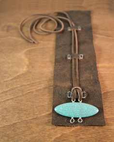 Leather - Turquoise howlite - Tie on strap -Length 7 - 8-inches -Height 2 1/2-inches  I have had these stone for quite some time but it took me forever to decide what to do with them. The unique shield shape along with the pop of bright turquoise against the dark chocolate of the leather are the things that make this cuff special. Weathered leather left raw at the edges forms the cuff which stands 2 1/2-inches tall. A turquoise colored howlite stone with sterling silver fittings is the focal…