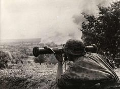 Dressed in summer camouflage, a Waffen-SS man estimate the range to a target for the artillery using a rangefinder 34 (Entfernungsmesser 34). Billowing skyward in the background is smoke from an earlier direct hit. Operation Barbarossa — 1941.