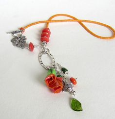 Polymer clay pendant with glass lampwork bead accents and small light orange African vinyl heishi beads. The length is 18 inches, with 4 1/2 inch