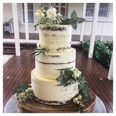 3 tier semi naked wedding cake - chocolate mud with chocolate swiss meringue buttercream, white chocolate citrus with malibu buttercream and red velvet with cream cheese buttercream all covered in vanilla buttercream.