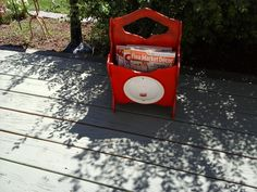 For Sale: RED MAGAZINE RACK - All wood rack with an enamel ware lid.   Painted in shades of red with distressing  and highlights of multi colors.  Non smoking shop.