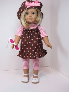 Kit is into poke-a-dots. She has a hat full of dots and a top to match. The stripped tee and leggings repeat the pink of hte dots and hat bow. White sandals and pink sunglasses complete her look.