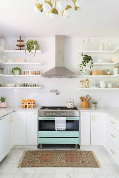 Nice kitchen design idea. White cabinets with gold accent handles, white open shelves and mint oven