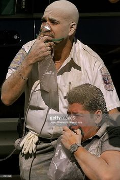A paramedic and a policeman breath oxygen after the first tower of the Twin Towers crumbled down after two planes hit the World Trade Center September 11, 2001 in New York City.