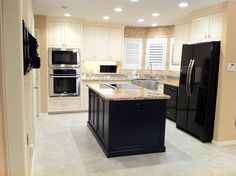 House 1- kitchen: custom inset cabinetry, travertine 2x4 and stainless backsplash, stainless farmhouse sink, porcelain tile floor, granite countertop, Electrolux oven & microwave, GE Profile induction with Kitchenaid pop up downdraft