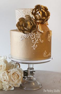 elegant gold metallic 2 tier wedding cake white scrolling and bold gold sugar flowers
