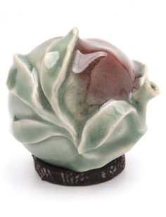 AN 18TH C. CHINESE/KOREAN WATER DROPPER IN THE SHAPE OF A CABBAGE Olive green with dark red glaze.. Sotheby's Chicago tag to underside. H. 7 cm.