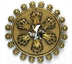 1800's brass button with little sunflowers around the edge. In the center are six filigree brass findings and a pinwheel shaped cut steel.