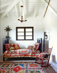 A Suzani quilt and kilim pillows give the guest room's Spanish Colonial-style daybed a dose of global pizzazz in Malcolm McDowell's 1920s Ojai farmhouse. The lantern is an early California cowboy lamp.