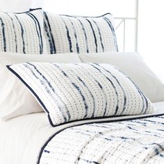 Inspired by traditional Indian kantha, the PCH Draftsman quilted pillow sham offers beds a soft cotton voile feel. Dappled indigo stripes create visual texture on a white backdrop. 100% cotton voile; 100% cotton batting; Kantha stitched; Solid indigo band/hem on all sides; Envelope back with ties; Machine wash cold separately with mild detergent; Hang to dry; Do not bleach; Do not dry clean; Standard: 20in W x 26in L; European: 26in W x 26in L
