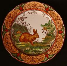 "Wedgwood Etruria polychrome transferware plate, with a rabbit before its warren in a pastoral setting, the rim printed with a series of griffins centering fruit-filled urns.  Various marks, impressed WEDGWOOD, and printed WEDGWOOD ETRURIA, ENGLAND with Rd.No.1474 in black. 10""  No chips or cracks. Crazing throughout."