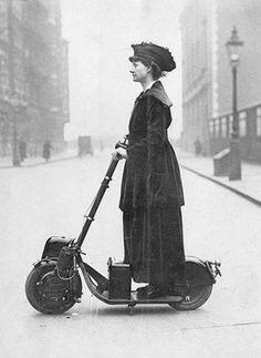 A woman rides an early electric scooter. [1916]