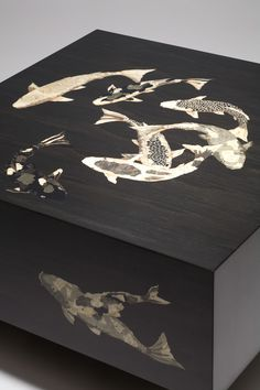 Koi Noir: a meditative slice of pond in slip-matched, rift-cut bog oak, its marquetry a restricted palette of black and white natural and dyed woods. 20 coats of hand-rubbed high gloss lacquer lend a reflective watery quality to the surface.