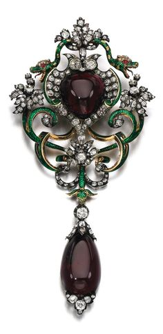 An antique gem set, enamel and diamond brooch, 1870s. Set with two foil backed garnets, surrounded by snake motifs applied with green enamel, cabochon rubies, circular-cut, cushion-shaped and rose diamonds. #antique #brooch