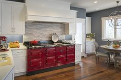Cherry red AGA cooker. Porcelanosa backsplash. Caesarstone. custom hood. white cabinets. Custom Kitchens by John Wilkins