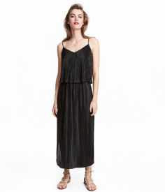 Calf-length dress in pleated, woven fabric with narrow shoulder straps. Elasticized seam under bust, wide flounce at top, and cut-out section at back. Wide skirt with rounded hem and slits at sides.