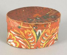 Small oval wallpaper box, mid 19th c., having an orange, yellow, and green floral decoration on a plum ground, 3'' h., 5 3/4'' w., 4 1/4'' d.