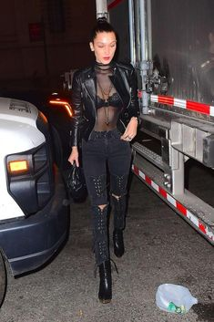 Bella Hadid wearing Charlotte Olympia Deborah Boots, Givenchy Mini Nightingale Bag in Embellished Black Leather, Basic Swim Black Long Sleeve Turtleneck Lui Bodysuit, Made Gold Bianca Jeans in Magnet and Charlotte Olympia Deborah Boots