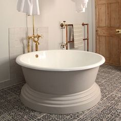 ROUND BATH WITH COPPER SHOWER  The designer  Patrick Williams has a lovingly restored new home in Bath, where he and his wife run a B&B in two rooms. Called Berdoulat & Breakfast, charming decorative touches abound, including this round bathtub with copper fixtures.