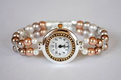 A two-toned Geneva watch with pearlized face and faux pearls in 4 different shades finish off this elegant stretchy beaded watch.