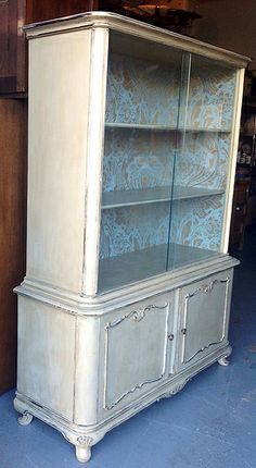"""""""Madame Stuttgart """"Re-Birth Date 11//6/13.This beautiful vintage china cabinet was refinished by Twisted Sister's Furniture w/Annie Sloan chalk paint in Country Grey w/dark & clear wax. It has a lovely blue/green damask wallpaper on the inside. Visit http://www.twistedsistersfurniture.com for more info."""