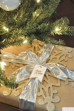 Christmas wrapping - brown paper, gold glittered snowflake, and silver bow.