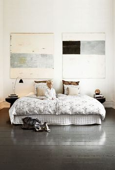 This is such an interesting bedroom.  No headboard, but the feature on that wall is the amazing artwork.  Nothing hectic, in keeping the rest of the colour tones in the room, which has been kept muted.  Yet the textures and soft patterns of this set up give this 'quiet ' space plenty of depth.  A room set up that has been well thought out.