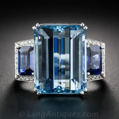 A gemmy, Santa Maria aquamarine, weighing 11 carats, displaying about the finest, deeply saturated color imaginable, glistens and glows between a matched pair of rich, royal blue, emerald-cut sapphires, weighing over one carat each, framed on three sides with small sparkling white diamonds. All of these are tastefully presented in a tailored mounting, expertly and sturdily crafted in gleaming 18K white gold. A singular and sublime. Currently ring size 7.