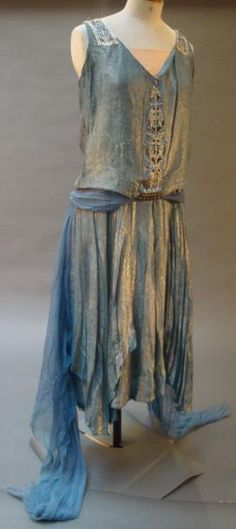 ~House of Worth, evening dress, ca. 1920.  Evening dress WORTH, circa 1920 blue and silver Lurex, central yoke straps and rhinestone out of beadwork. Belt draped chiffon lavender draped low on the hips and floating panels in the back. Seam sealed background apricot satin dress. White woven label on white background~